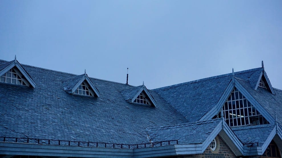Image of a house with skylights and a black shingle roof.